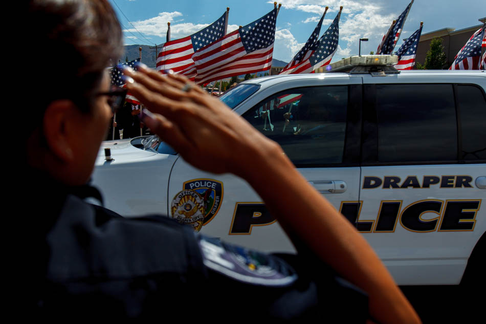 Flags fly as the funeral procession for Sgt. Derek Johnson, the Draper police officer who was shot to death on Sunday morning, passes through Draper Friday, September 6, 2013
