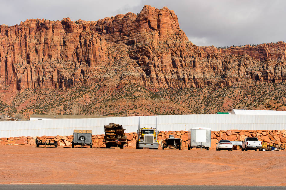The view from Espresso Creek - Vermillion Cliffs, the wall around the FLDS storehouse, and some trucks and trailers.