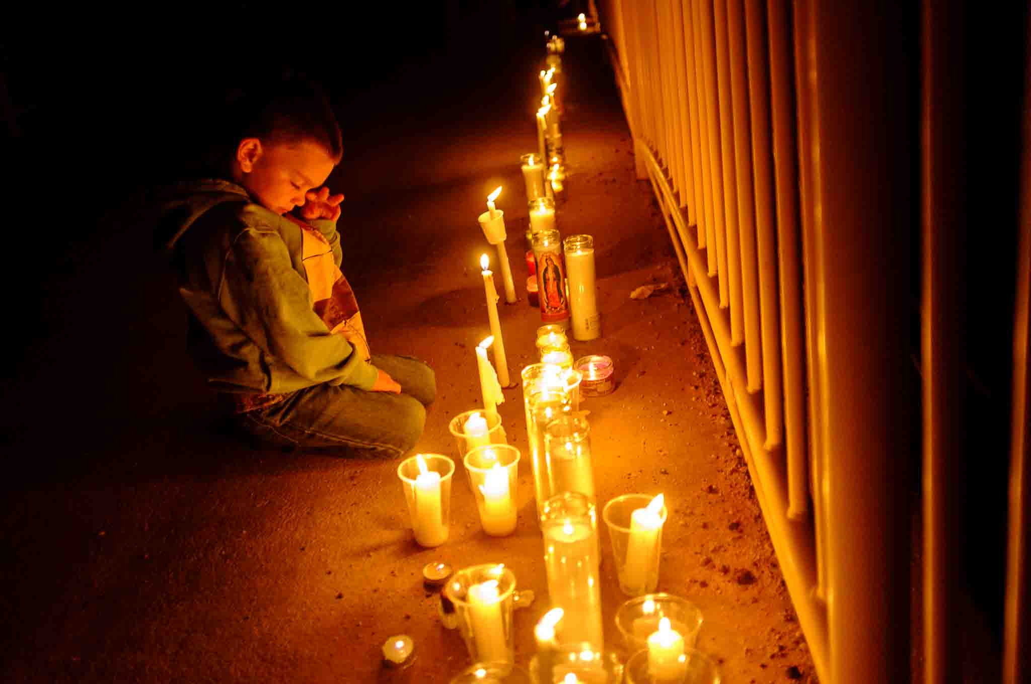 Photo: Drexton Musser, 4, looks down at candles on a bridge over Short Creek as residents of Hildale, UT and Colorado City, AZ, hold a memorial to the victims of the 2015 flash flood