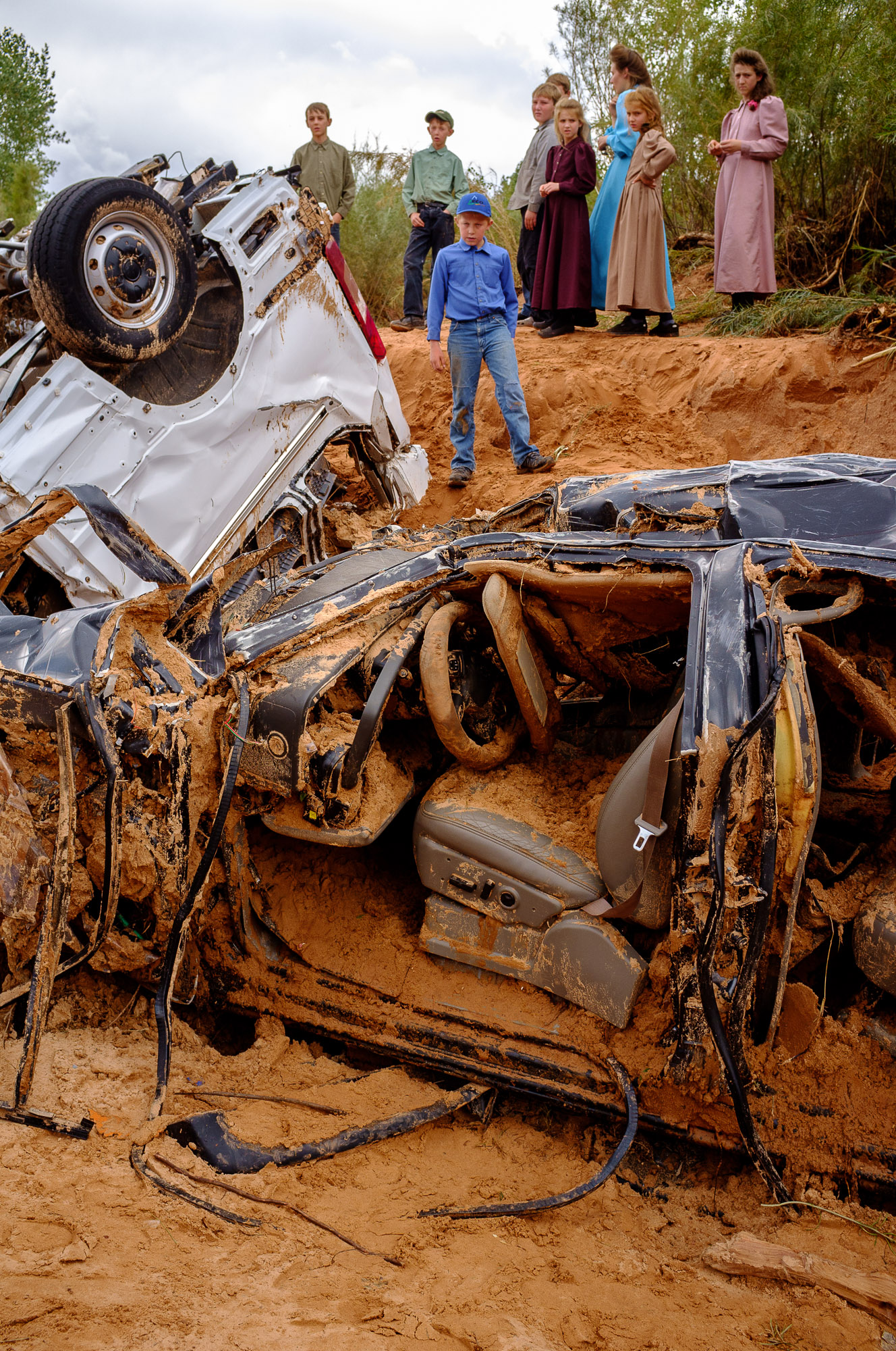 Children from the FLDS polygamous sect look at the wreckage of the two vehicles that had been swept away in a flash flood in the Short Creek Wash, killing thirteen (with another victim still missing)